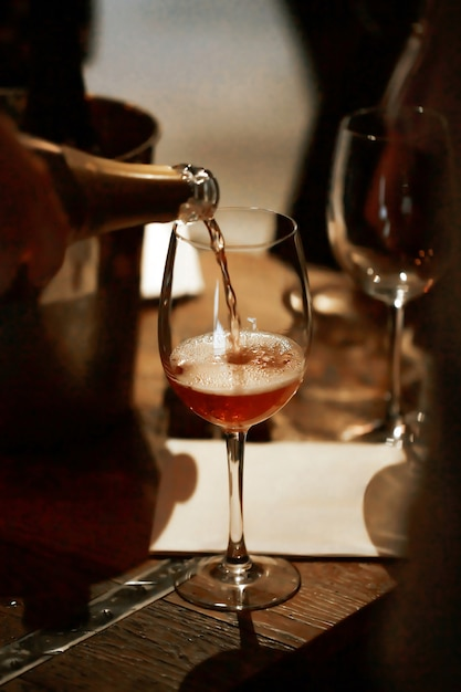 Un Filet De Champagne Rose Remplit Le Verre Sur La Table En Bois. Photo Premium