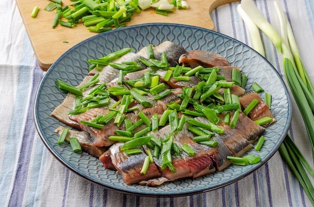 Filet de hareng coupé en morceaux avec des oignons verts sur une assiette bleue. fond de bois clair. Photo Premium