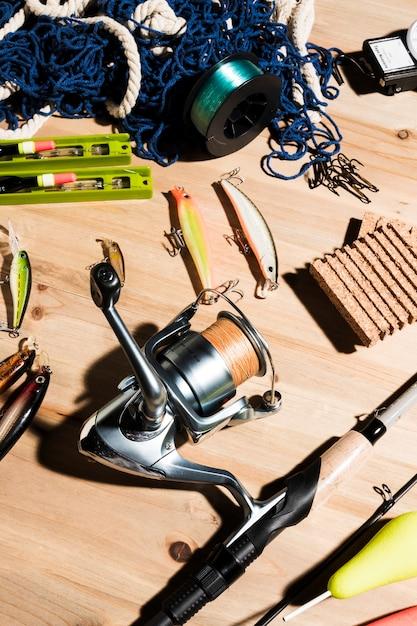 Filet de pêche; moulinet de pêche; leurres et canne à pêche sur fond en bois Photo gratuit