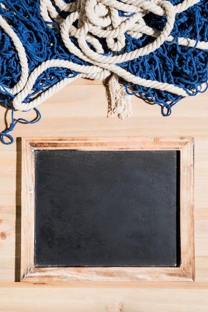 Filet de pêche sur le tableau blanc sur la surface en bois Photo gratuit