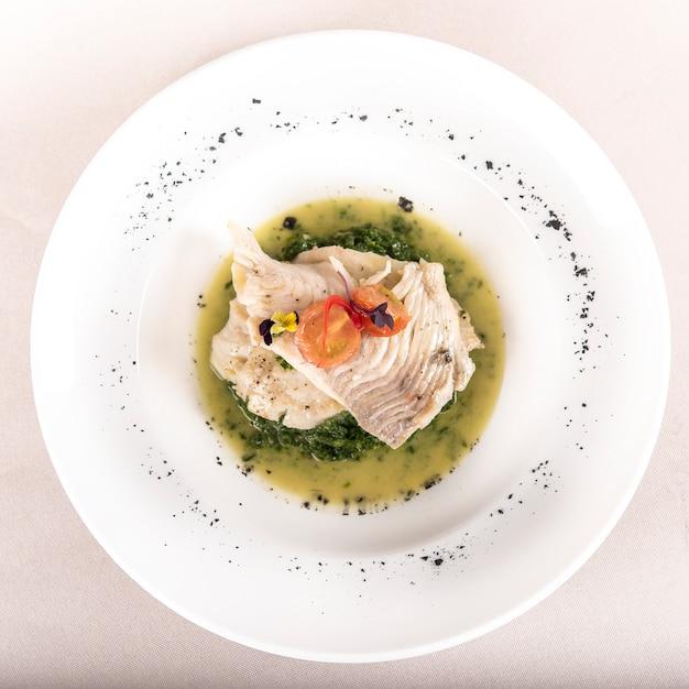 Filet de perche aux épinards, sauce et tomates, décoré de fleurs mangeables et feuille rouge Photo Premium