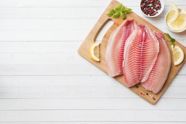 Filet de poisson cru de tilapia sur une planche à découper au citron et épices Photo Premium
