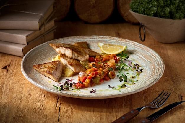 Filet De Poisson Sandre Et Purée De Pommes De Terre, Plat Sur Une Assiette Sur Une Table En Bois. Photo Premium