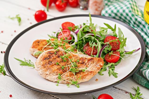 Filet de poulet grillé et salade de légumes frais, tomates, oignons rouges et roquette. Photo Premium