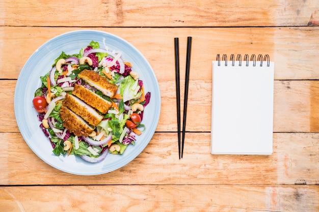 Filet de poulet avec salade sur une assiette en céramique; baguettes et bloc-notes spirale blanc sur table en bois Photo gratuit