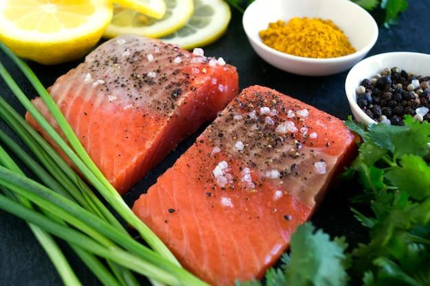 Filet de saumon cru et ingrédients pour la cuisson sur un fond sombre dans un style rustique. vue de dessus Photo Premium
