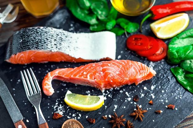 Filet de saumon cru et ingrédients pour la cuisson sur un mur sombre. Photo Premium