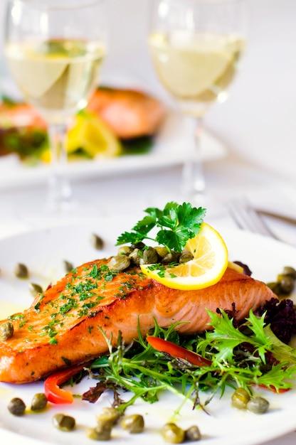 Filet de saumon grillé avec légumes et un verre de vin blanc. Photo Premium