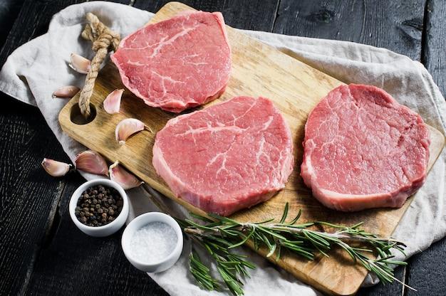 Filet de steak de bœuf cru sur une planche à découper en bois Photo Premium