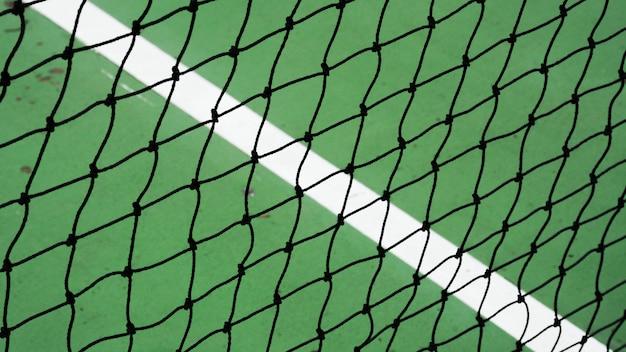 Filet de tennis noir sur un court de ciment vert Photo Premium