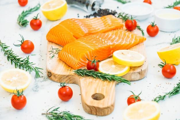 Filet de viande de saumon cru et frais sur une planche à découper en bois Photo gratuit