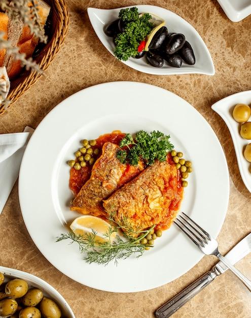 Filets De Poisson à La Sauce Tomate Servis Avec Petits Pois Citron Et Fines  Herbes | Photo Gratuite