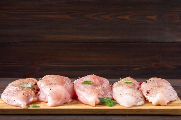 Filets de poulet cru sur une planche à découper dans le contexte d'une table en bois. Photo Premium