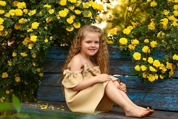 Fille De 4 Ans Assise Sur Un Banc Sous Un Buisson De Roses Jaunes. Dans Une Robe Beige, Regardant Dans Le Cadre Avec Un Sourire Sur Son Visage. Cheveux Bouclés, Pieds Nus. Photo Premium