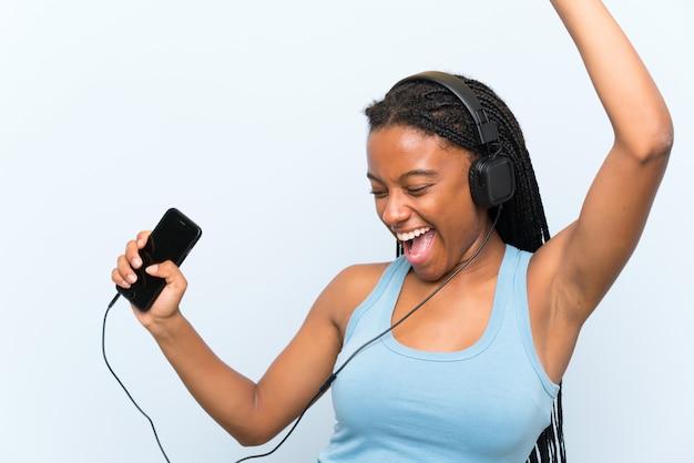 Fille Adolescente Afro-américaine Avec De Longs Cheveux Tressés, écoute De La Musique Avec Un Téléphone Portable Et Danse Photo Premium