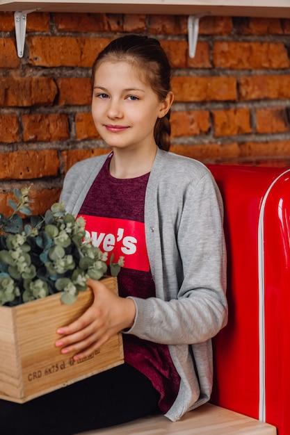 Fille Adolescente Assise à La Cuisine. Cuisine De Style Loft Avec Murs En Briques Et Réfrigérateur Rouge. Photo Premium