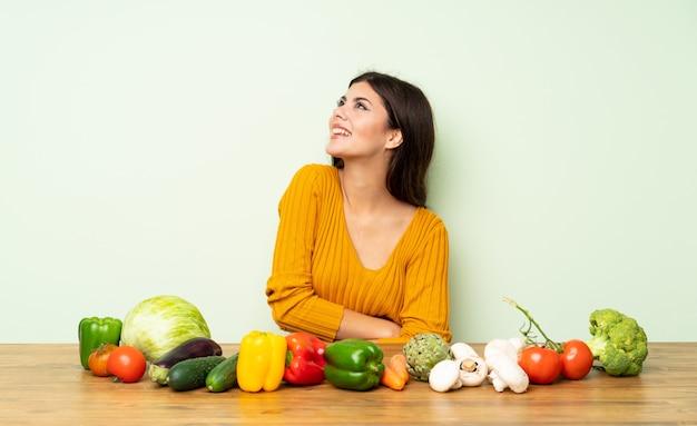 Fille adolescente avec beaucoup de légumes heureux et souriant Photo Premium