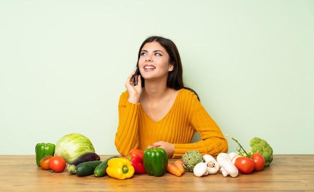 Fille adolescente avec beaucoup de légumes, tenant une conversation avec le téléphone mobile Photo Premium