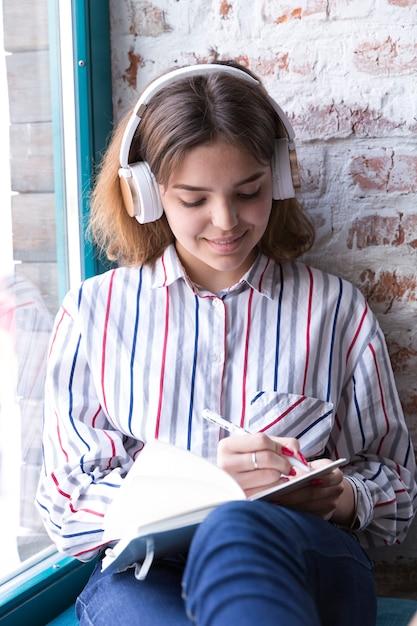 Fille adolescente dans les écouteurs assis avec cahier ouvert et écrit à la main Photo gratuit