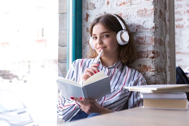 Fille adolescente dans les écouteurs assis avec un livre ouvert et regardant la caméra Photo gratuit