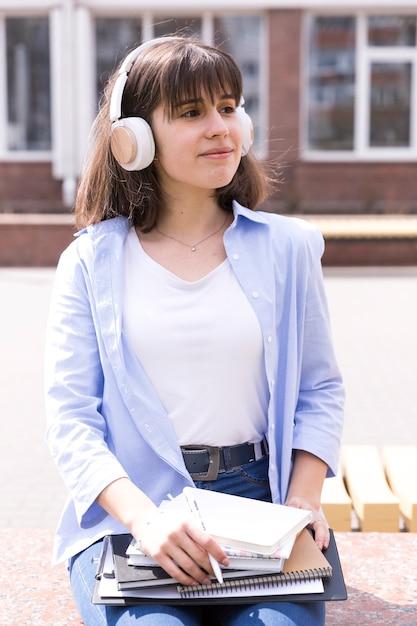 Fille adolescente dans les écouteurs assis avec des livres Photo gratuit
