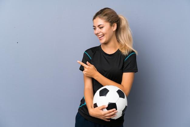 Fille adolescente de football américain sur un mur gris pointant sur le côté pour présenter un produit Photo Premium