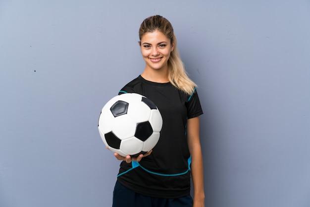 Fille adolescente joueur de football blonde sur mur gris Photo Premium