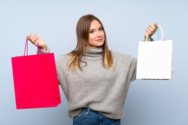 Fille adolescente avec pull tenant beaucoup de sacs Photo Premium