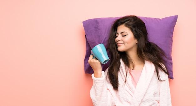 Fille adolescente en robe de chambre sur fond rose et tenant une tasse de café Photo Premium