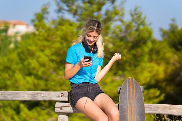 Fille adolescente avec skate à l'extérieur avec téléphone en position de victoire Photo Premium
