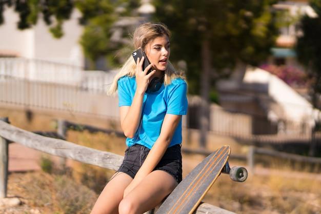 Fille Adolescente Avec Skate En Plein Air En Conversation Avec Le Téléphone Mobile Photo Premium