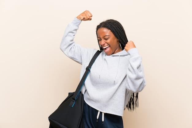 Fille adolescente sportive afro-américaine avec de longs cheveux tressés célébrant une victoire Photo Premium