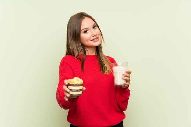Fille adolescente tenant un verre de lait et un muffin Photo Premium