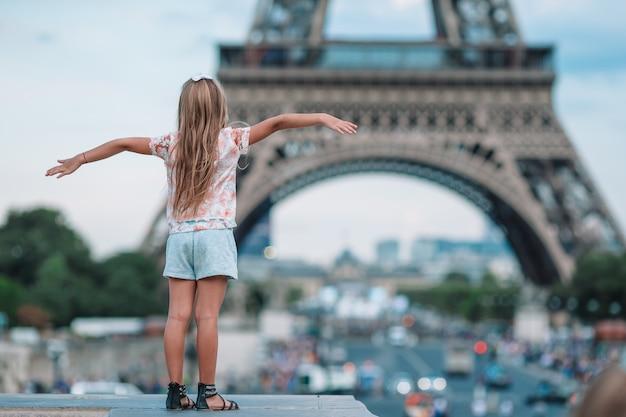 Fille adorable bambin à paris sur la tour eiffel pendant les vacances d'été Photo Premium