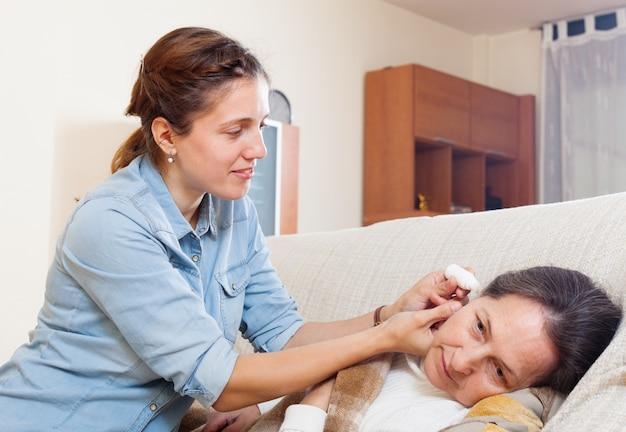 Fille adulte dégoulinant des gouttes d'oreille à la mère mûre Photo gratuit