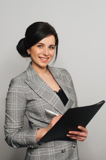 Fille d'affaires en costume avec un dossier de documents et un sourire amical. Photo Premium