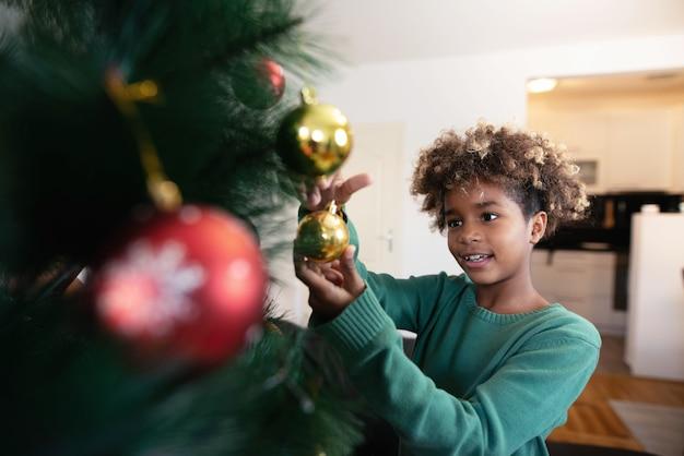 Fille Afro-américaine De Décoration De Sapin De Noël Dans Un Intérieur Confortable Photo gratuit