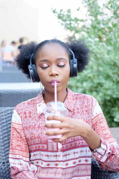 Fille Afro Noire En Robe Ethnique Avec Un Casque Et Les Yeux Fermés Assis Dans Un Café En Plein Air, écouter De La Musique Et Boire Un Cocktail De Lait Photo Premium