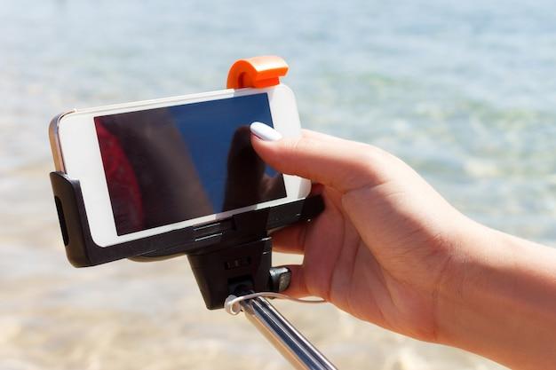 Fille ajuste la caméra sur le bâton de selfie dans la mer Photo Premium
