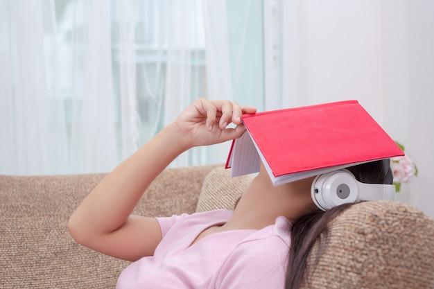 Fille allongée sur le canapé en écoutant de la musique et en lisant des livres. Photo gratuit