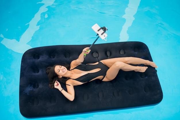 Fille allongée sur un matelas gonflable dans la piscine et fait une photo de selfie au téléphone avec un bâton de selfie Photo Premium