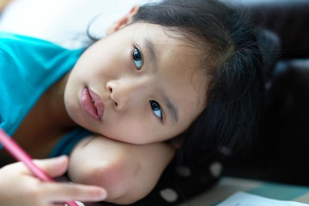Fille allongée pour écrire un cahier au sol Photo Premium