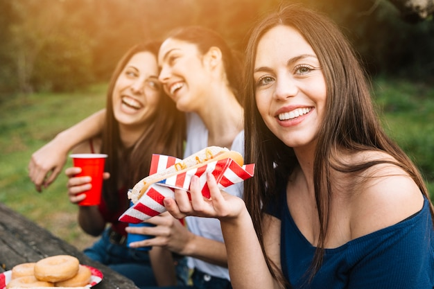 Fille avec des amis au repos dans le parc Photo gratuit