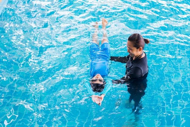 Fille apprenant à nager avec un entraîneur à la piscine Photo Premium