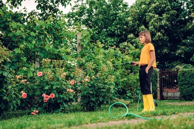 Fille arrosant des fleurs dans le jardin Photo Premium