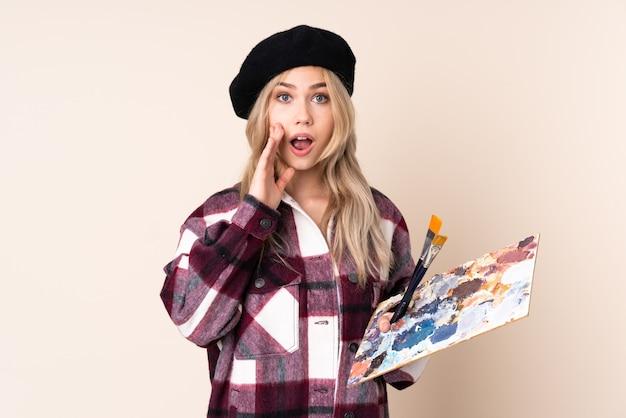 Fille Artiste Adolescent Tenant Une Palette Isolée Sur Un Mur Bleu Avec Surprise Et Expression Du Visage Choqué Photo Premium