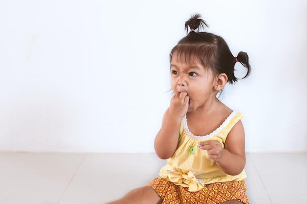 Fille asiatique bébé mignon bébé manger des nouilles par elle-même et faire un désordre sur son visage et sa main Photo Premium