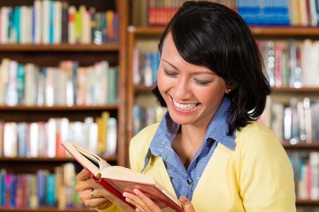 Fille asiatique dans la bibliothèque en lisant un livre Photo Premium