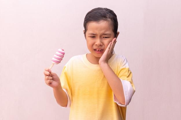 Fille Asiatique Avec Des Dents Hypersensibles Manger Manger Un Popsicle Gelé Coloré En été Photo Premium
