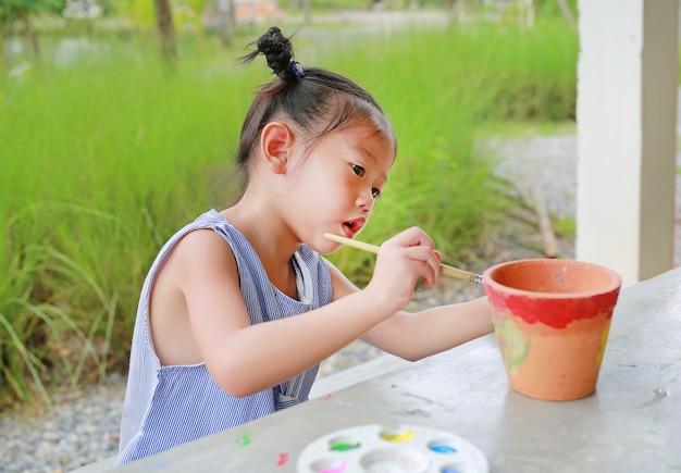 Fille asiatique enfant peindre sur plat en terre cuite. Photo Premium